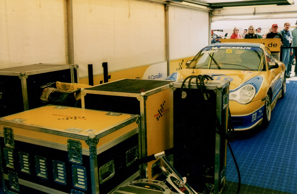 Amptown Cases für den Rennsport mit einem Rennwagen im Hintergrund