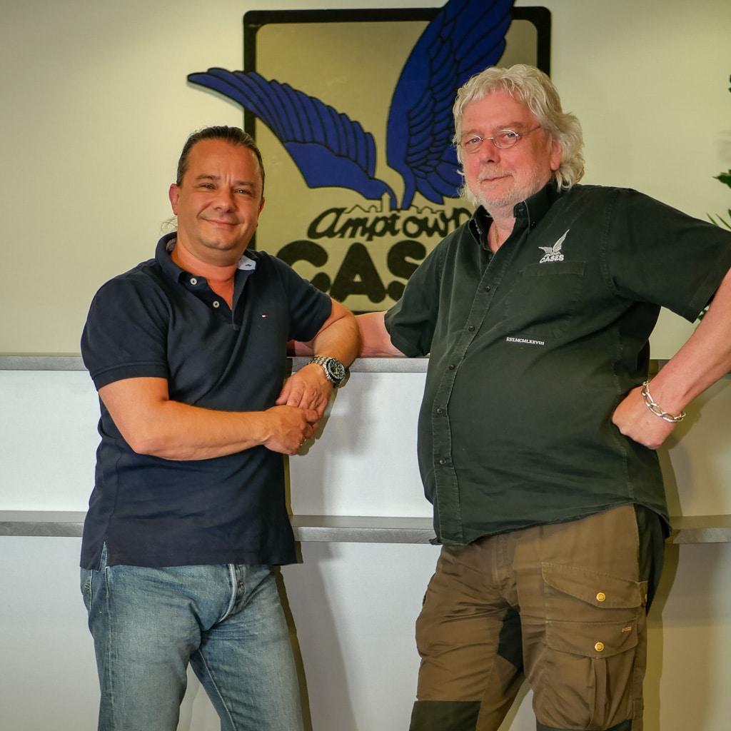 "Geschäftsführer Oliver Wüpper und Michael ""Mick"" Fischer vor dem Amptown-Logo an der Wand"