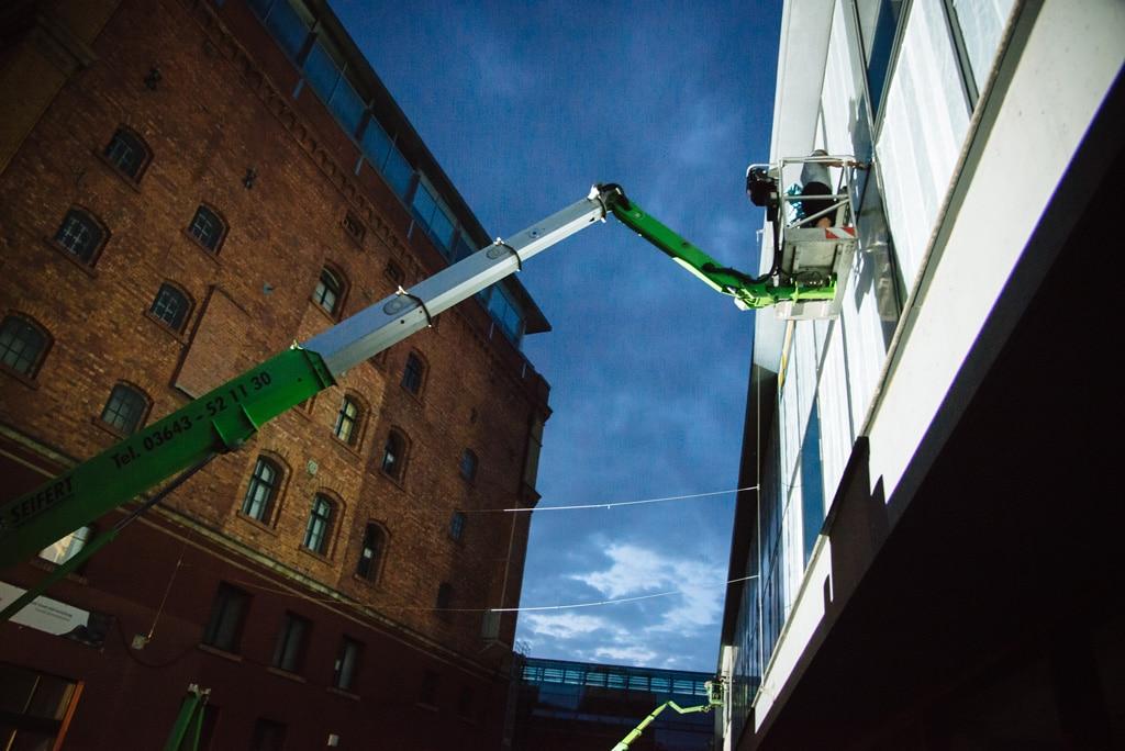 Anbringen einer Folie an die Front des Universitätsgebäudes der Bauhaus-Uni Weimar zur Vorbereitung für den Einsatz der Videotechnik