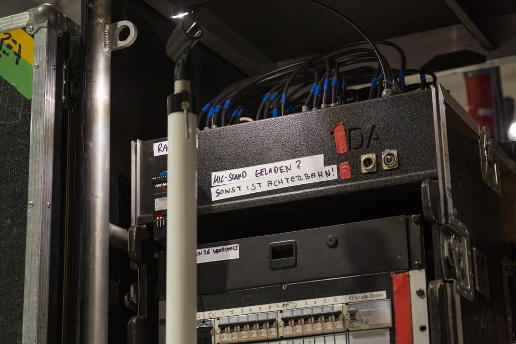 Mikrofonständer in Neonröhren-Optik vor einem Rack
