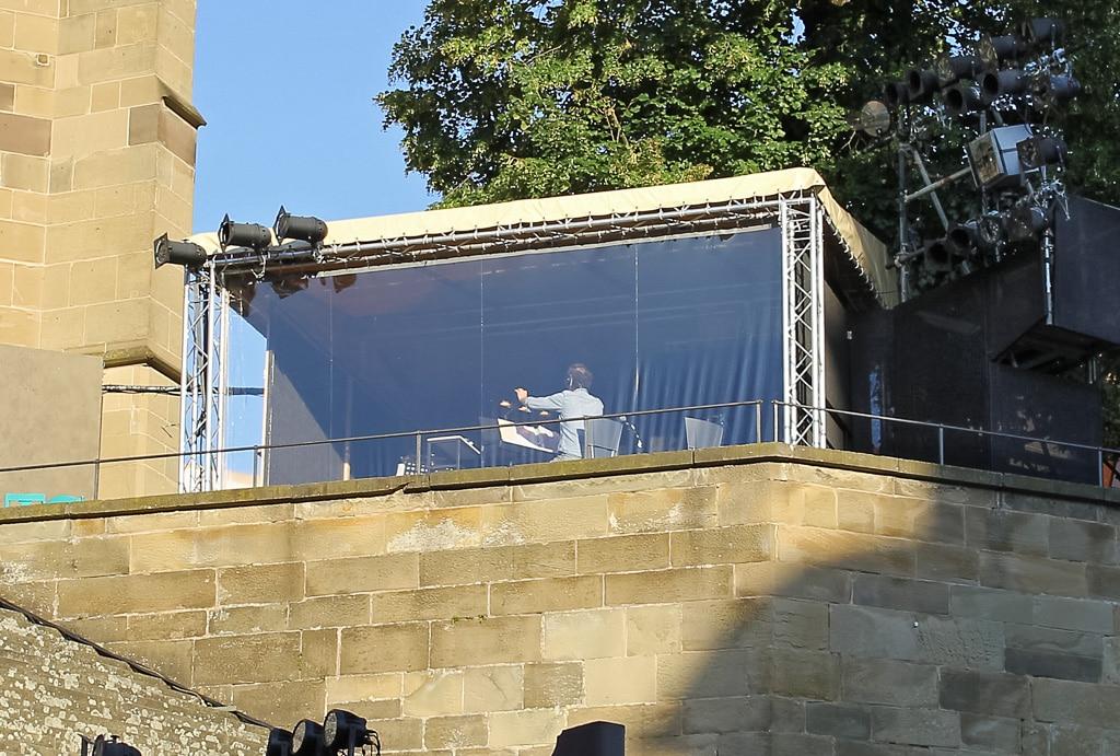 Bandpodest neben der Kirche. Hinter den Fenstern wird dirigiert