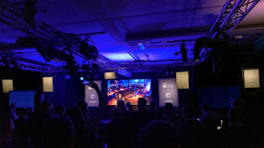 Frontbeschallung, links oben im Dunkeln ein Lautsprecher-Ring über einer kleinen Bühne im Publikum