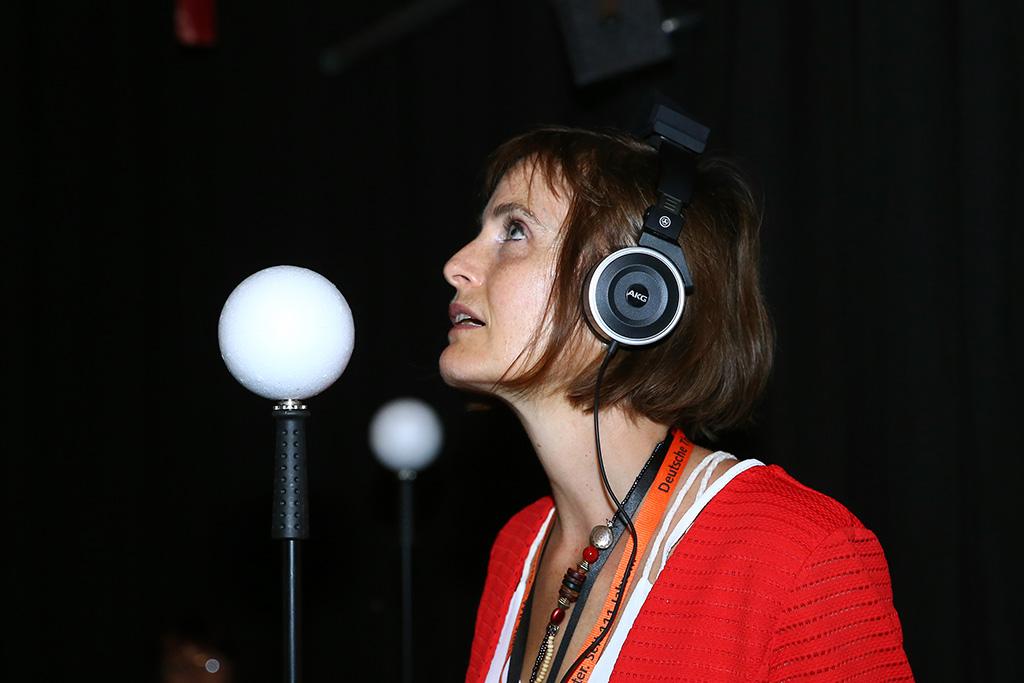 Frau mit Kopfhörern vor schwarzem Hintergrund